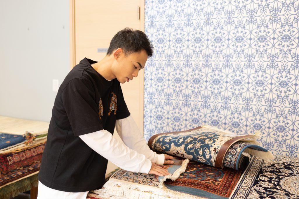 絨毯の織り方について説明するあっきー