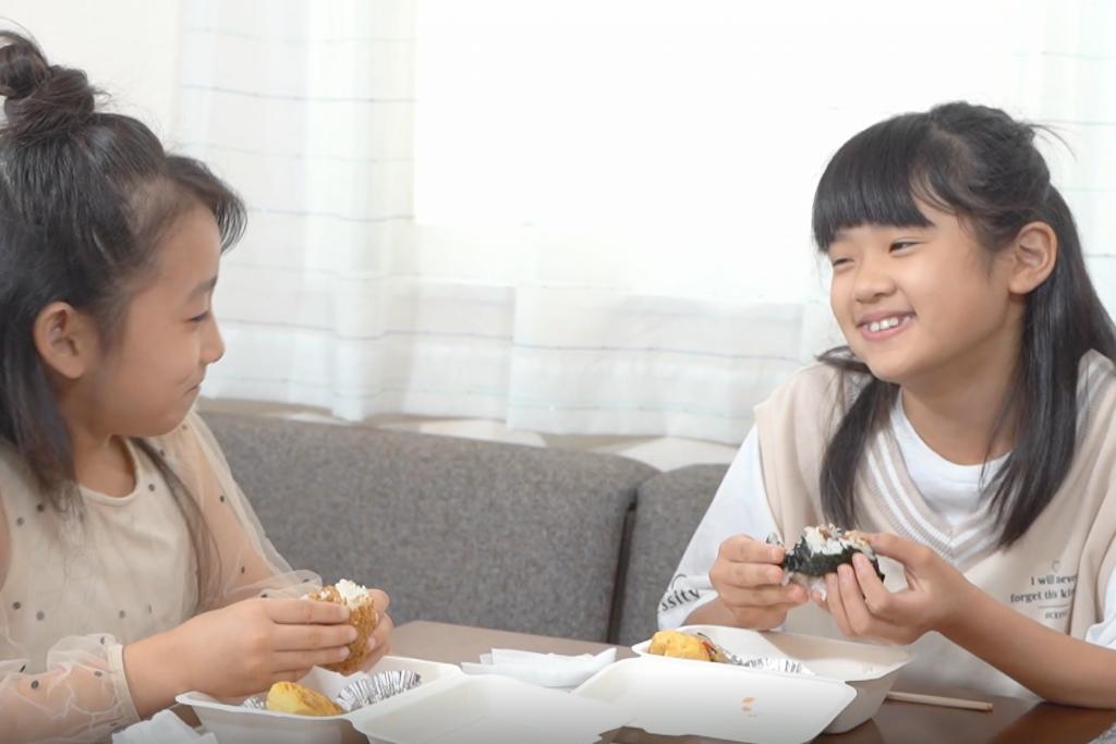 にぎりむすびの食事を食べる子どもたち